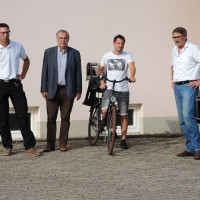 Bastian Hümmer, Bürgermeister Bernhard Ruß, Matthias Naumann und Paul Hümmer vor dem vorgeschlagenen Standort der beantragten Fahrradabstellfläche